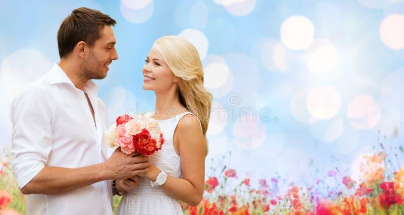 Glückliches Paar mit Blumen über Lichthintergrund stockfoto