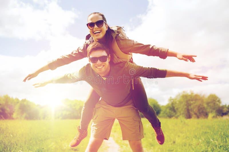 Glückliches Paar mit den Rucksäcken, die Spaß draußen haben lizenzfreies stockfoto