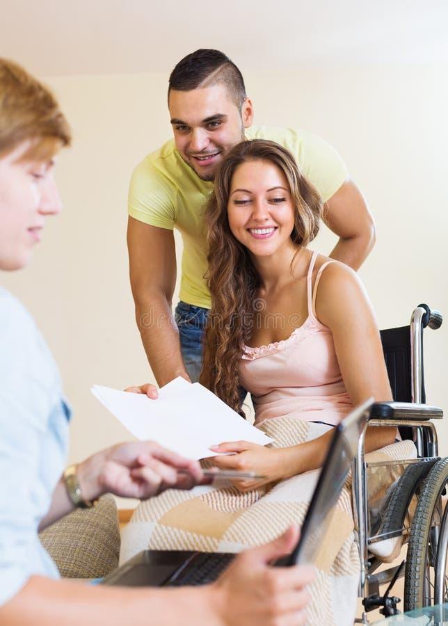 Glückliches Paar mit der behinderten Frau, die mit Bankangestellte spricht stockbilder