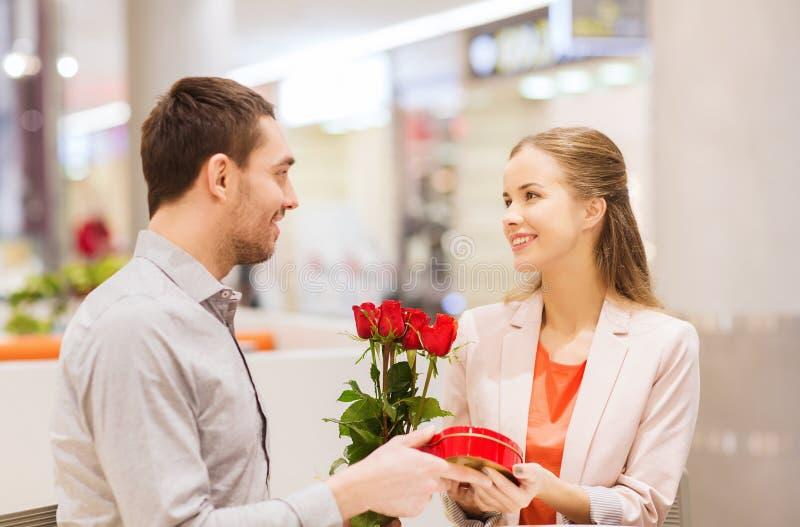 Glückliches Paar mit Geschenk und Blumen im Mall lizenzfreie stockfotos