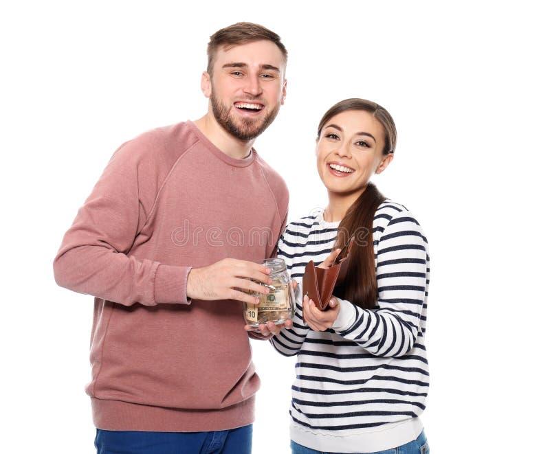 Glückliches Paar mit Glasgefäß voll von Dollarbanknoten und -geldbörse auf weißem Hintergrund Dollar in einer Flasche stockbild