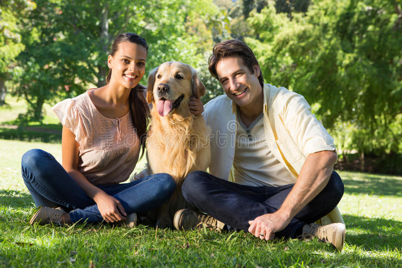 Glückliches Paar mit ihrem Schoßhund im Park lizenzfreies stockfoto