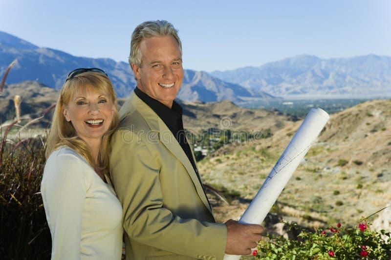 Glückliches Paar mit Landschaft im Hintergrund stockfotos
