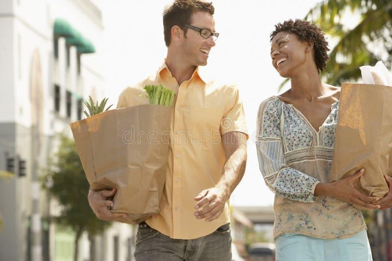 Glückliches Paar mit Lebensmittelgeschäften draußen gehend stockbild