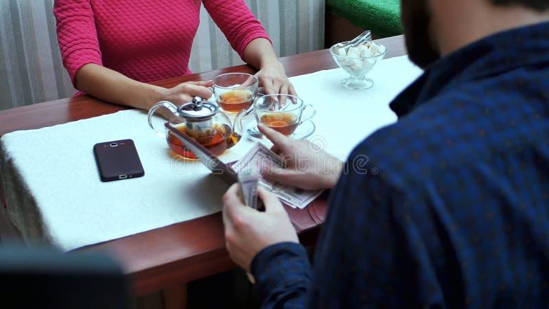 Glückliches Paar mit Lohnliste der Geldbörse am Restaurant mit Dollarbargeld stockbilder