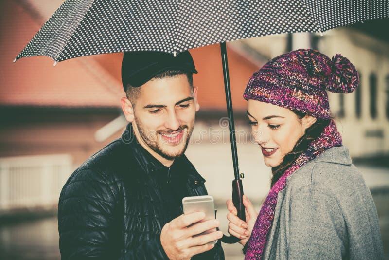 Glückliches Paar mit Regenschirm in der Stadt unter Verwendung eines Handys stockbilder