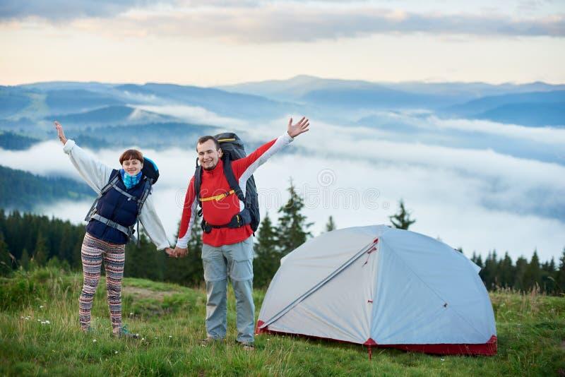 Glückliches Paar mit Rucksäcken nähern sich Zelt gegen Hintergrund von schönen Landschaftsbergen lizenzfreies stockfoto
