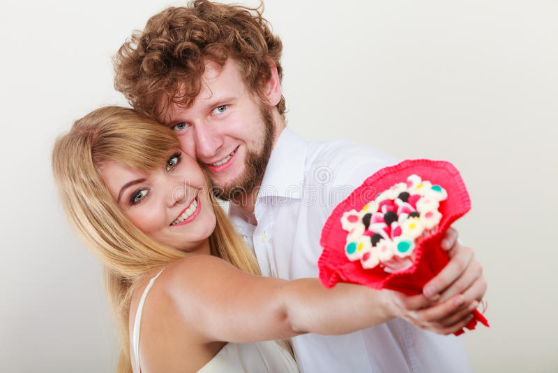 Glückliches Paar mit Süßigkeitsbündelblumen Liebe lizenzfreie stockfotos