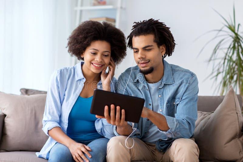 Glückliches Paar mit Tabletten-PC und -kopfhörern zu Hause stockfotografie