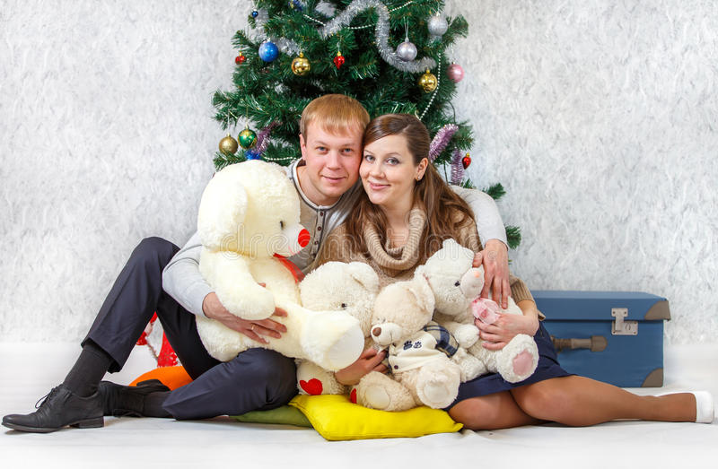 Glückliches Paar mit Teddybären nähern sich Weihnachtsbaum lizenzfreie stockbilder