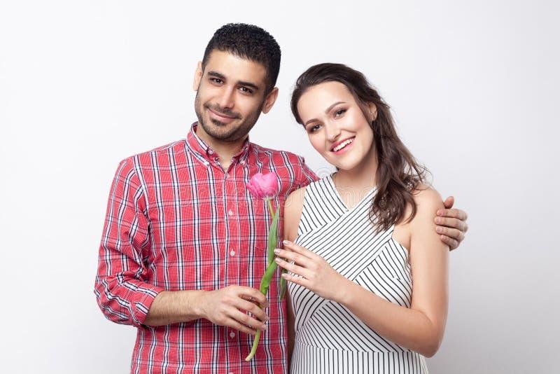 Glückliches Paar mit Tulpe, lächelnd, umarmen und betrachten Kamera Porträt des gut aussehenden Mannes im roten karierten Hemd un stockbilder