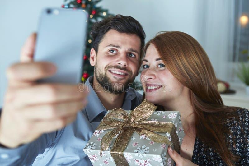 Glückliches Paar nimmt ein selfie mit Geschenk lizenzfreies stockfoto
