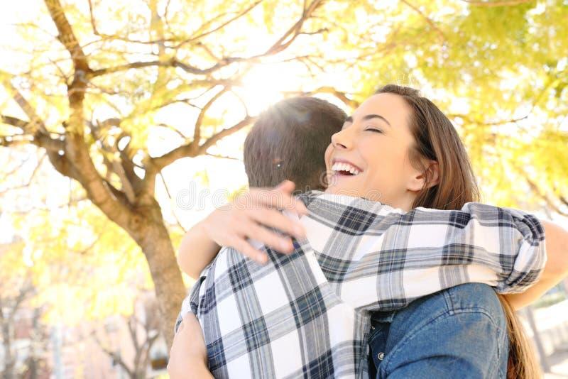 Glückliches Paar oder Freunde, die in einem Park umarmen lizenzfreie stockfotografie