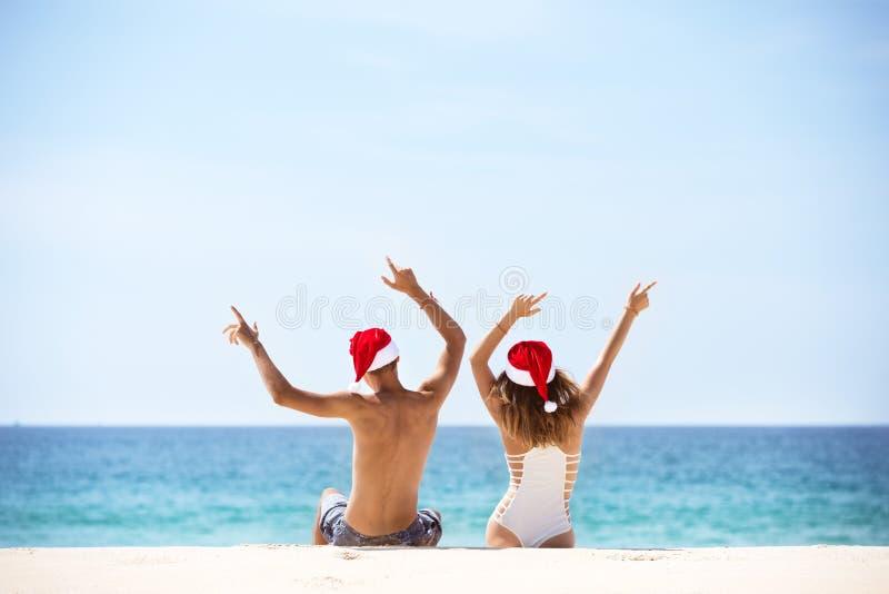 Glückliches Paar in Sankt-` s Hüten am tropischen Strand lizenzfreie stockfotografie