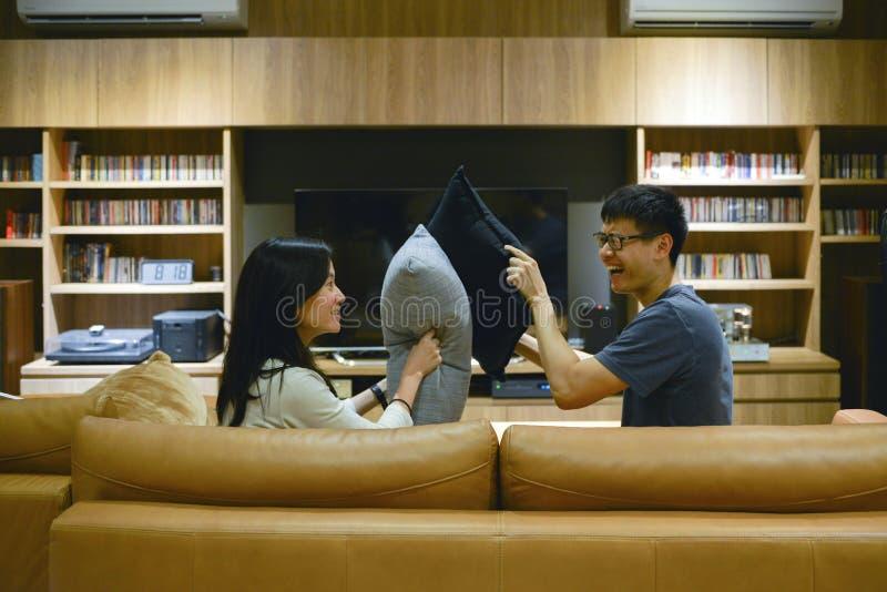 Glückliches Paar schlug sich mit Kissen im Wohnzimmer nachts stockfotos
