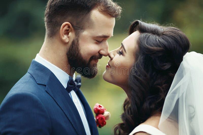 Glückliches Paar von den Jungvermählten, die einander in einem Park closeu betrachten stockfotos