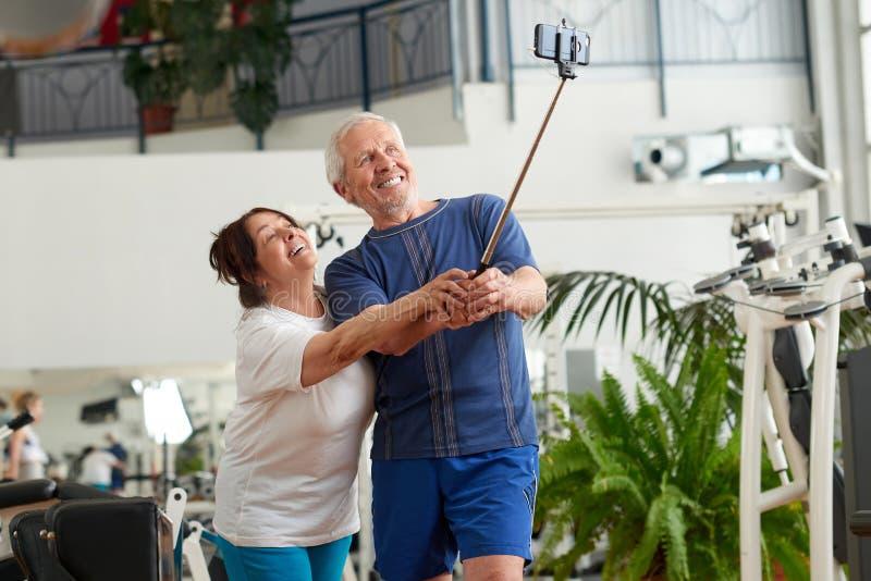 Glückliches Paar von den Senioren, die monopod an der Turnhalle verwenden lizenzfreies stockfoto