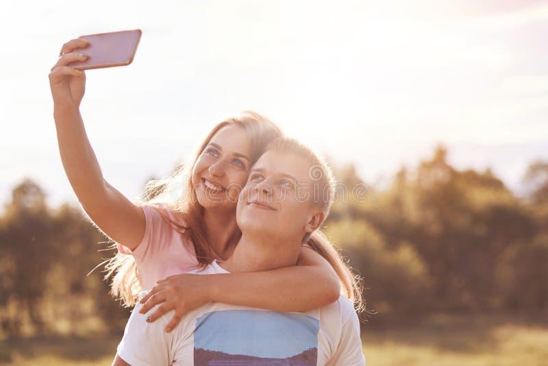 Glückliches Paar von Knaben umfassen und betrachten froh intelligentem Telefon, macht geschossene selfie während recreat draußen  lizenzfreies stockbild