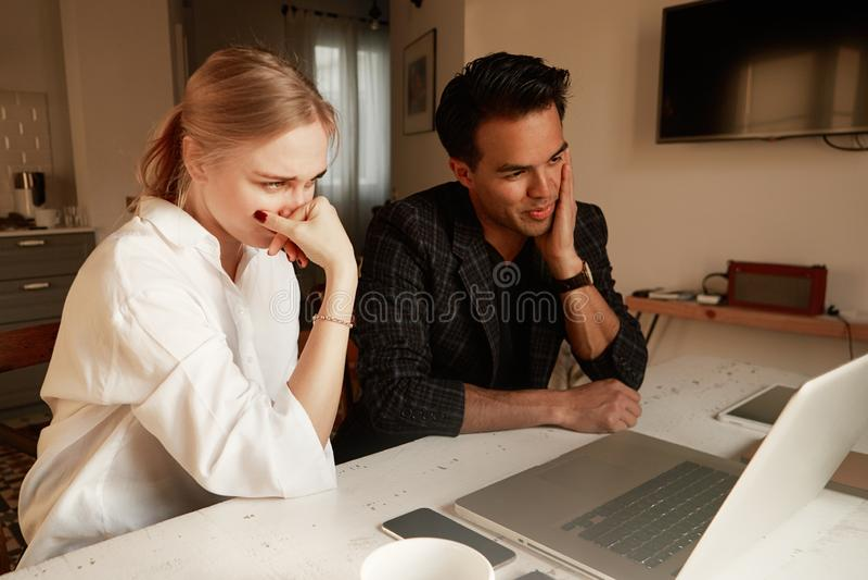 Glückliches Paar, welches das Geschäft zusammenarbeitet im kleinen Büro auf dem Laptop tätigt stockfotografie