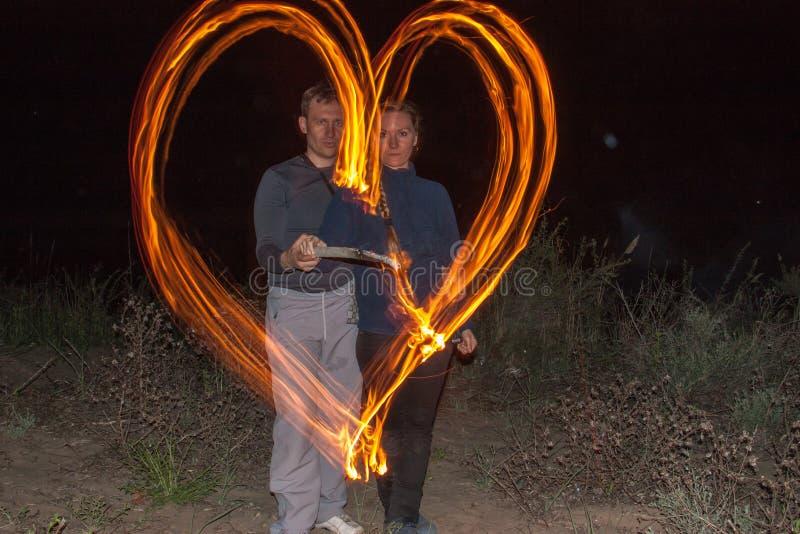 Glückliches Paar, welches die Herzflammen des Feuers als Symbol der Liebe malt stockbilder