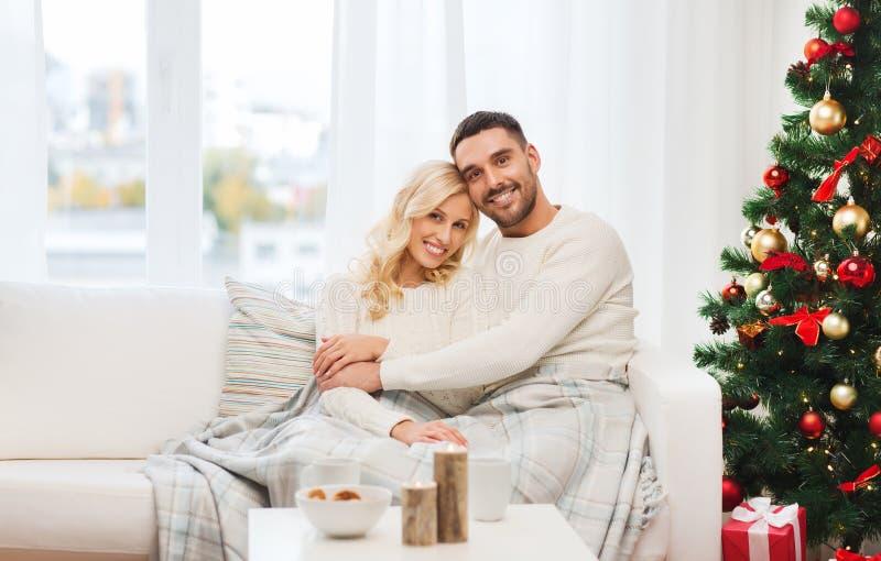 Glückliches Paar zu Hause mit Weihnachtsbaum stockfotos