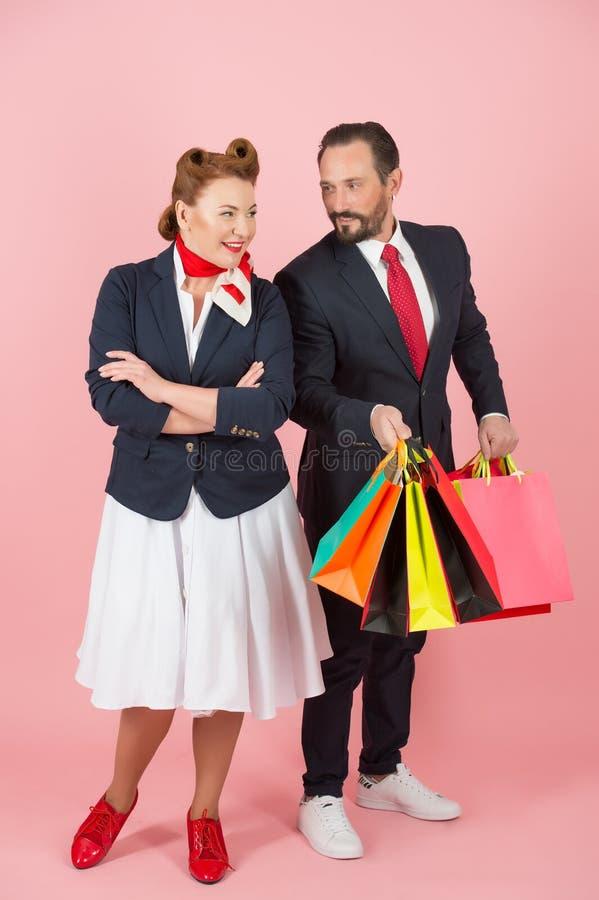 Glückliches Paar zur Einkaufszeit Mann hält Los farbige Taschen mit Geschenken für Frau Stift-oben redete Paare auf rosafarbenem  stockbilder