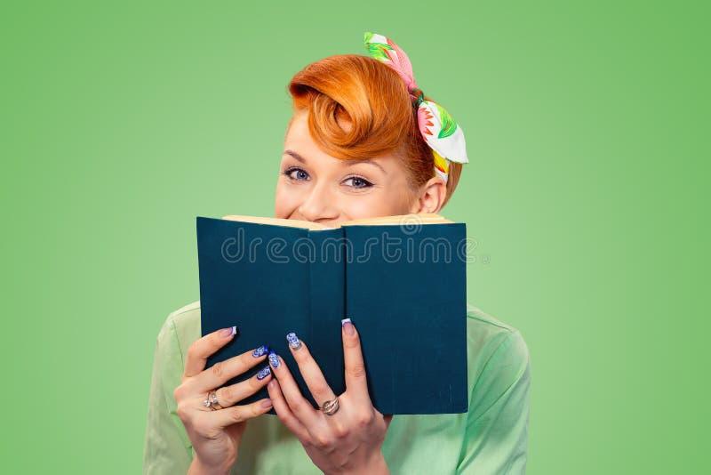 Glückliches Pinupmädchen, das hinter einem Buch sich versteckt lizenzfreies stockbild