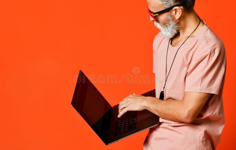 Glückliches Porträt des modischen Pensionärs den Gebrauch des neuen Laptops genießend lizenzfreie stockfotos