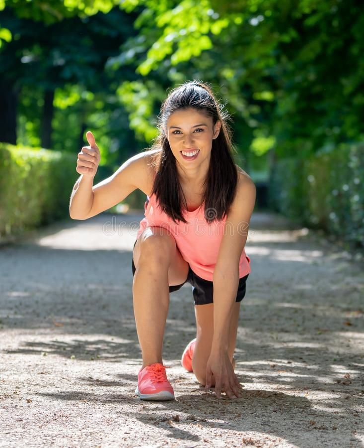 Glückliches Porträt des sportiven Mädchens lächelnd an der Kamera mit ihren Daumen oben stockfoto