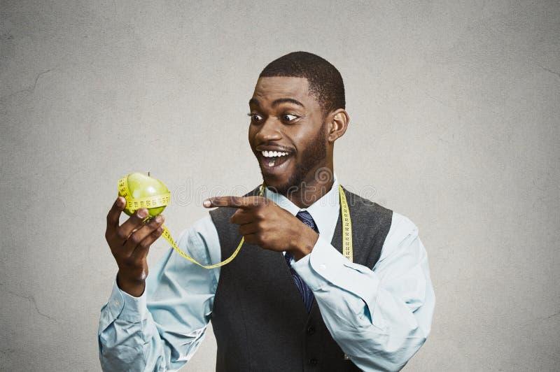 Glückliches Professionellerzeigen des Porträts, grünen Apfel halten lizenzfreie stockfotos