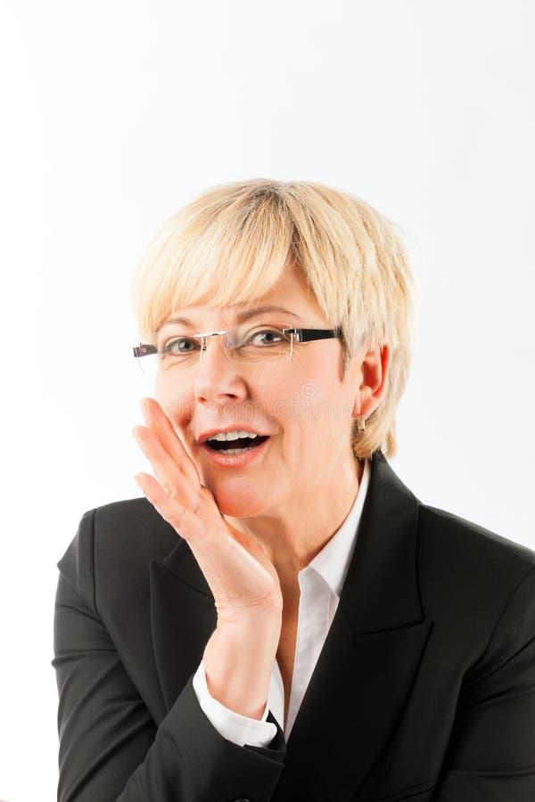 Glückliches reifes Geschäftsfrausprechengeheimnis lizenzfreies stockfoto
