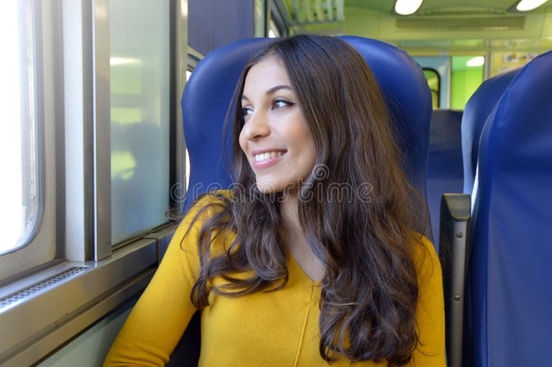 Glückliches reisendes Schauen der jungen Frau aus Fenster heraus beim Sitzen im Zug lizenzfreies stockbild