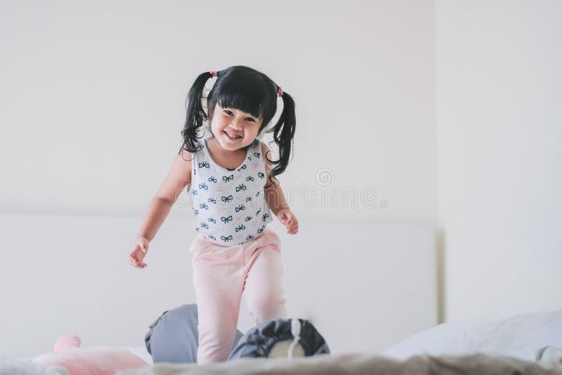 Glückliches reizendes Kinderporträt Ein drei Jahr-altes Mädchen im Glück-Moment im Schlafzimmer lizenzfreies stockbild