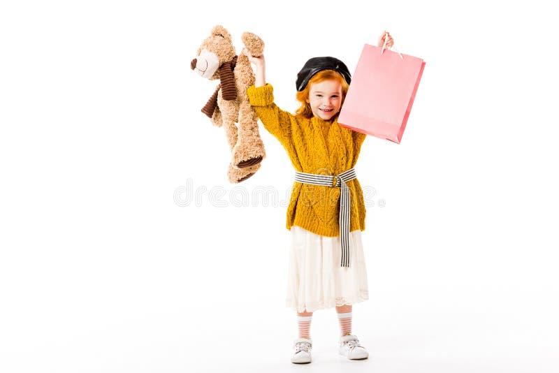 glückliches Rothaarigekind, das Einkaufstasche und Spielzeug in den Händen über Kopf hält lizenzfreies stockbild