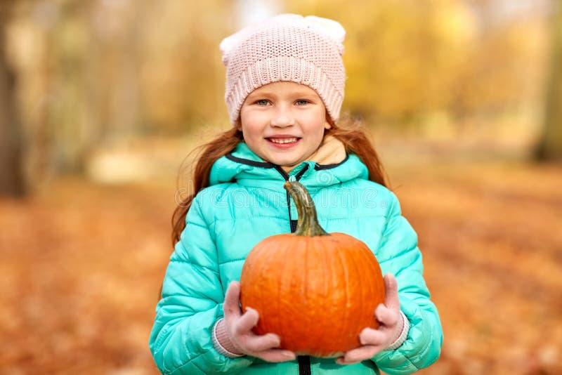Glückliches Rothaarigemädchen mit Kürbis am Herbstpark lizenzfreie stockfotografie
