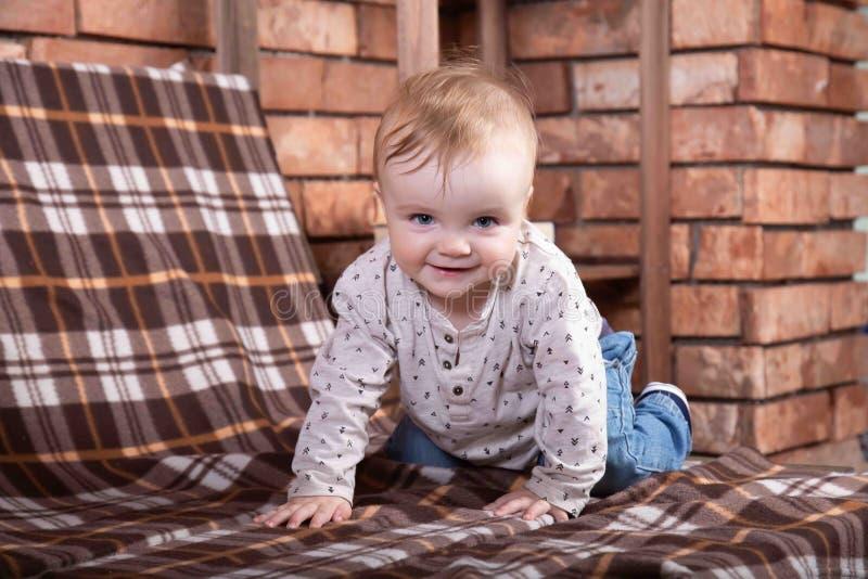 Glückliches Säuglingsbaby, das auf alle fours kriecht Wand der roten Backsteine auf dem Hintergrund lizenzfreie stockfotos