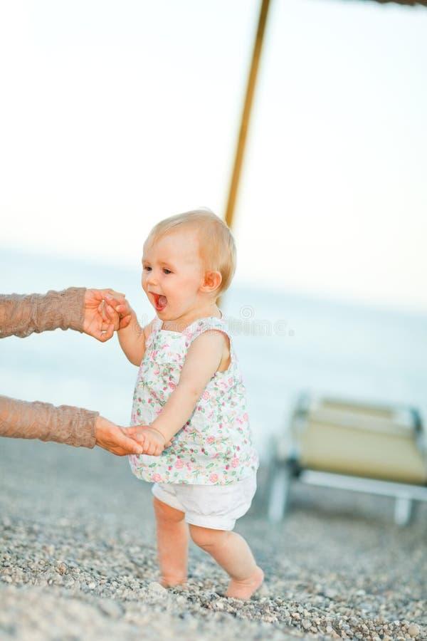 Glückliches Schätzchen auf dem Strand, der versucht zu gehen zu beginnen lizenzfreie stockfotos