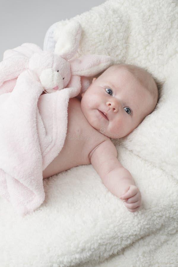 Glückliches Schätzchen mit rosafarbener Spielzeughäschendecke stockbild