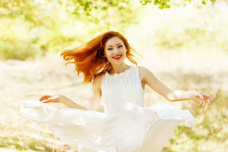 Glückliches schönes Ingwermädchen in einem weißen Weinlesekleid des Flugwesens in t lizenzfreie stockbilder