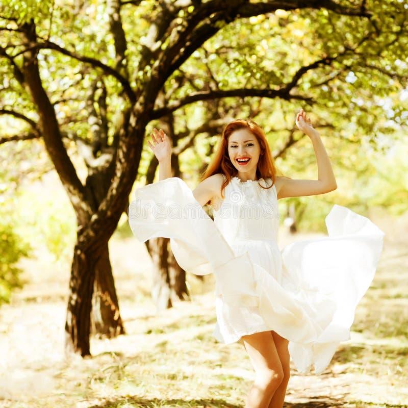 Glückliches schönes Ingwermädchen tanzt in eine Flugwesenweißweinlese stockfoto