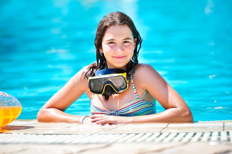 glückliches schönes jugendlich Mädchen, das am Pool lächelt lizenzfreie stockfotografie