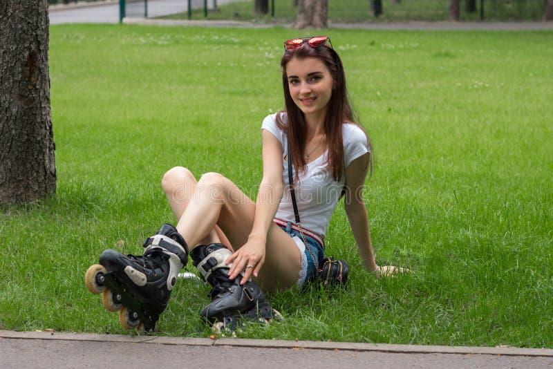 Glückliches schönes junges Mädchen, das auf dem Gras in den Rollen sitzt lizenzfreies stockbild