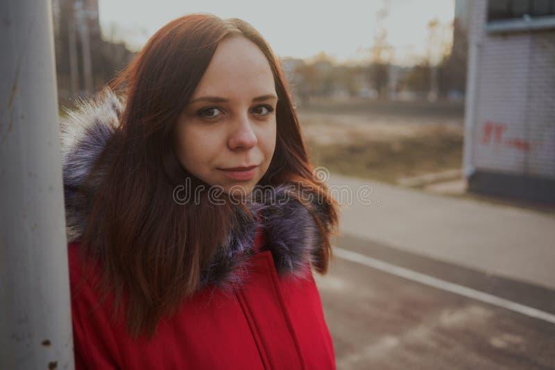 Glückliches schönes junges Mädchen in einer roten Jacke, die draußen an einem bewölkten Tag aufwirft lizenzfreie stockfotos