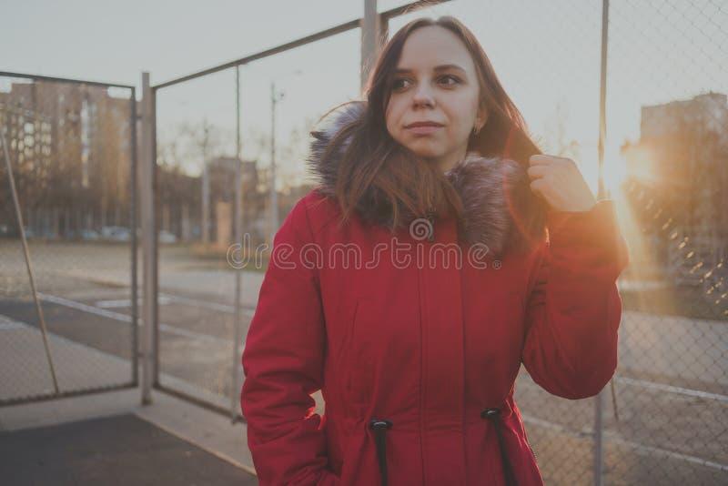 Glückliches schönes junges Mädchen in einer roten Jacke, die draußen an einem bewölkten Tag aufwirft lizenzfreies stockbild