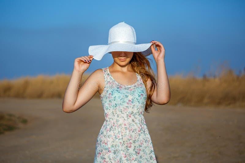 Glückliches schönes junges Mädchen mit Hut auf natürlichem Hintergrund am sonnigen Tag stockfotos
