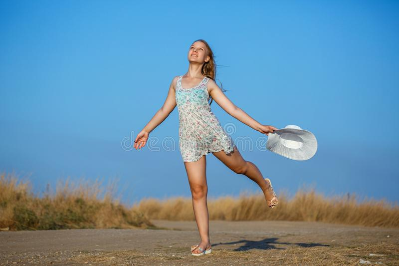 Glückliches schönes junges Mädchen mit Hut auf natürlichem Hintergrund am sonnigen Tag lizenzfreies stockfoto