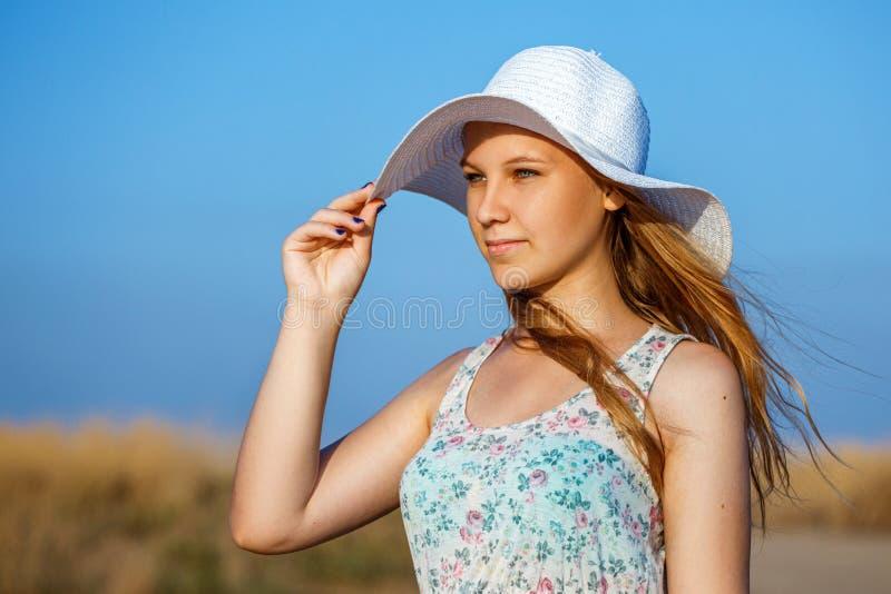Glückliches schönes junges Mädchen mit Hut auf natürlichem Hintergrund am sonnigen Tag stockbild