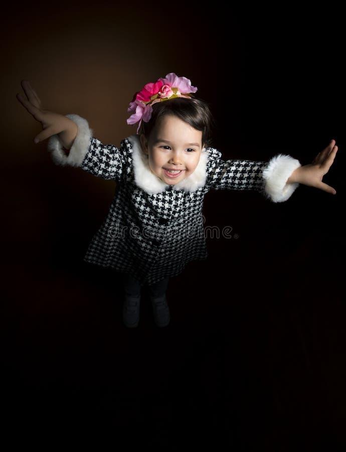 Glückliches schönes kleines Mädchen, das mit ihren Händen oben auf schwarzem Hintergrund, Atelieraufnahme schreit stockbilder