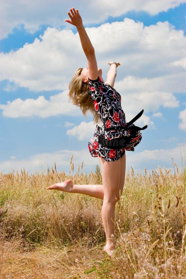 Glückliches schönes Mädchen, das in die Luft springt lizenzfreies stockfoto