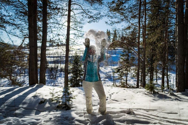 Glückliches schönes Mädchen, das im Schnee bis zum Tag spielt stockfotos
